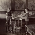 Photo of two young male students studying a map of the United States.