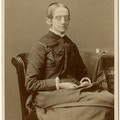 Seated portrait of Laura Bridgman with her hands in her lap. Several spools of thread are visible on the tabletop beside her.