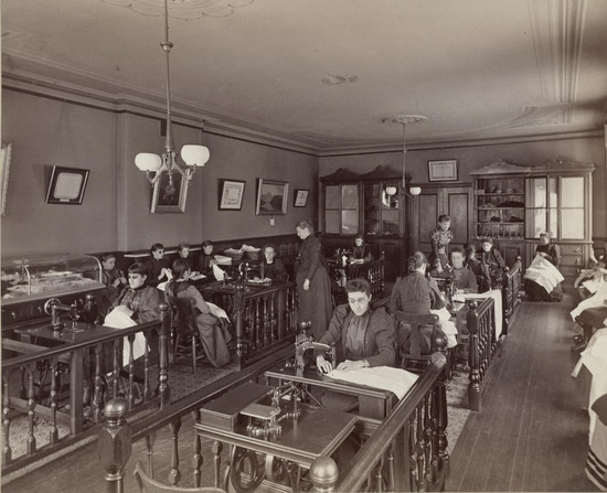 Girl's sewing class from upper grammar at the the Perkins Institution and Massachusetts School for the Blind in South Boston. The sewing room has eight or more sewing machine tables in two rows with railings sectioning off the work stations. Students sit on benches along the walls with sewing in their laps.