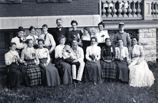 Gathering of pupils with deafblindness and teachers from five institutions in Buffalo, New York in 1901. Reunion funded by William Wade. Students and teachers are arranged in two arching lines outside on the grass with front row seated and back row standing. From the Perkins School for the Blind: Edith M. Thurston, Thomas Stringer, Miss Helen S. Conley, Edith Thomas, Vina C. Badger, and Elizabeth Robin. From the South Dakota School for the Blind: Dora Donald (Superintendent) and Linnie Haguewood.From the Ohio Institute for the Deaf: Ada Buckles, Ada E. Lyon, and Leslie F. Oren. From the New York Institute for the Deaf: Myra L. Barrager, W. H. Van Tassell, Orris Benson, Catherine Pederson, Florence G. S. Smith and Katie McGirr.