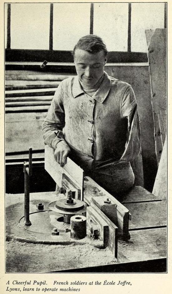 A man with one arm works on machine in a woodworking shop.