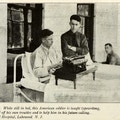 Man in bed uses typewriter while man in uniform looks on.