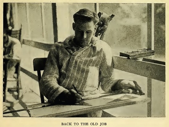 Young man sits working at drafting board,