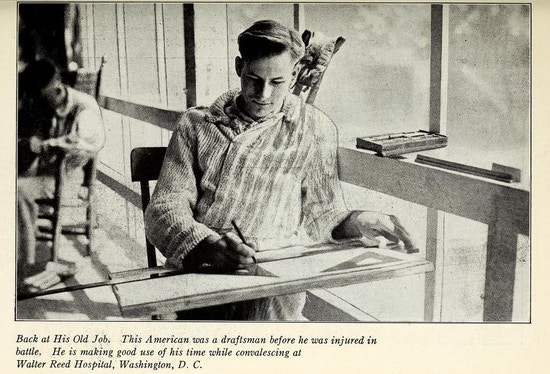 Young man sits at drafting table next to large window.