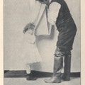 Small child dries hands and face with a roller towel also used by a man.
