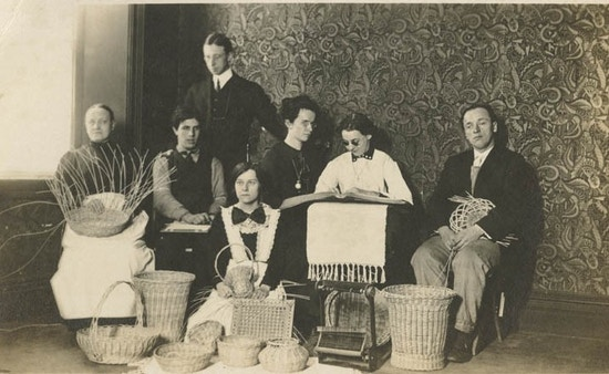 Group photograph of male and female visually impaired basket weavers, photographed with baskets.