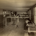 Boys' caning shop, Main building, Perkins Institution, South Boston, Mass. Showing Mr. Thomas J. Carroll, instructor. The boys stand at tall work benches with chair seats to be caned clamped at chest height. They each have long lengths of caning materials that they weave across the wooden frames.