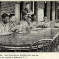 Six African American men sit around a table while a white man in uniform looks on.