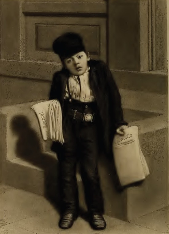 A boy wearing high-waist pants, an over-sized jacket, and a hat holds newspapers in both hands.