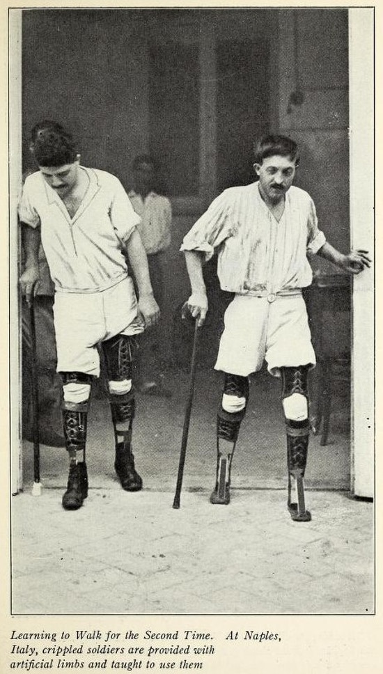 Two men, both amputees, walking with prosthetic legs.