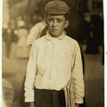 Boy with cap stands in street holding a newspaper.