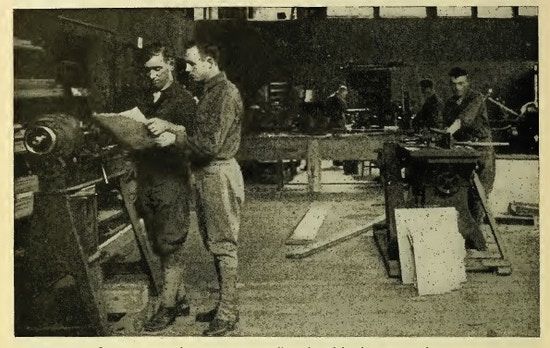Men working at carpentry machinery.