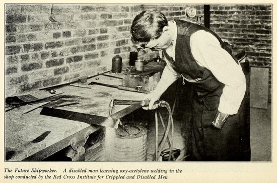 Man with one hand uses welding equipment at a work bench.