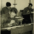 Three men sitting at desks, working with compasses.