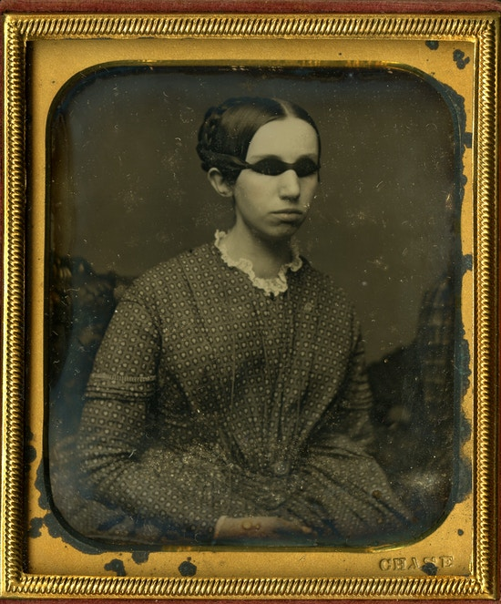 Portrait of Laura Bridgman as a young woman wearing a patterned dress with lace collar. Her hair is braided and pinned up with a part down the middle. The Daguerreotype photograph is housed in a small leather case with a patterned red velvet lining surrounded by a gold mat board and embossing.