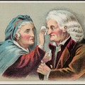 Elderly woman applying liquid to elderly man's eye.