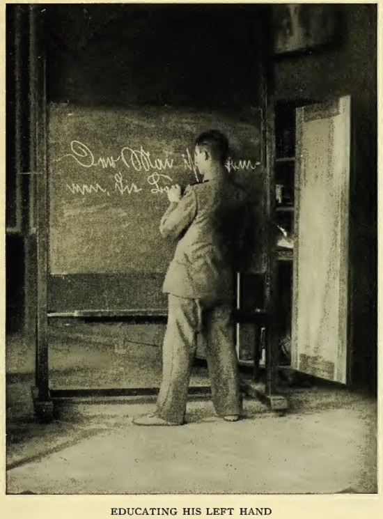 Man writing on a blackboard with his left hand.
