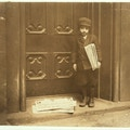 Young boy in hat stands before large door holding newspapers.