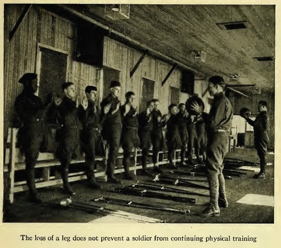 About a dozen one-legged men stand in a row, facing men holding exercise balls.  crutches lie on the floor.