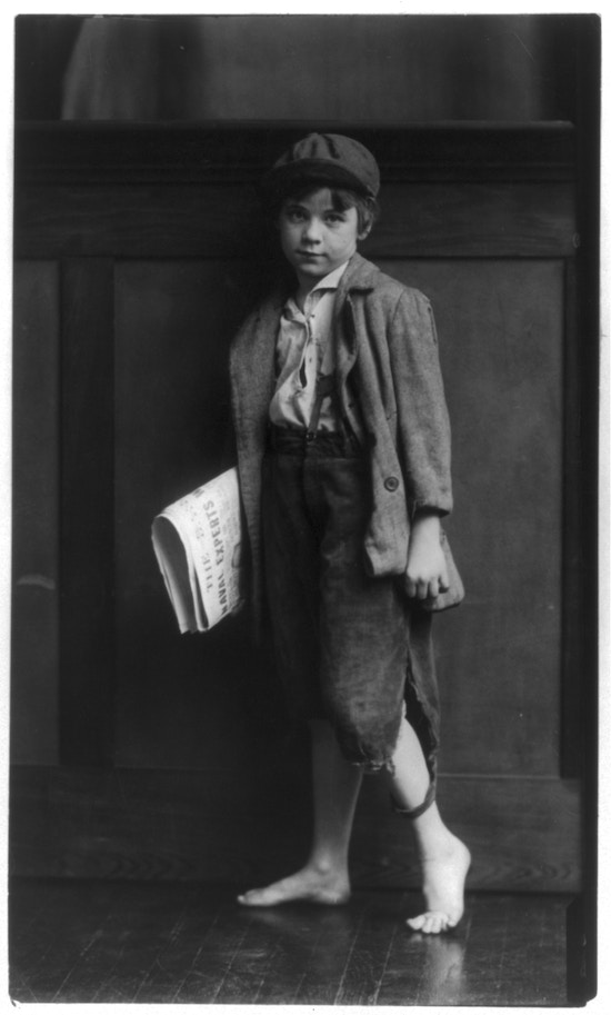 Bare-footed boy holding newspapers.