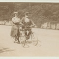 Keller, facing three quarters right, riding tandem bike with man, facing camera.