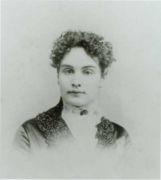 Young Sullivan facing camera, curly hair, dark dress, white lace collar with dark broach at throat.