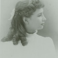 Young Helen Keller facing right, white bow in hair, white dress.