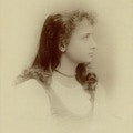 Young Helen Keller, side view looking right, white dress, necklace, hair down loosely arranged.