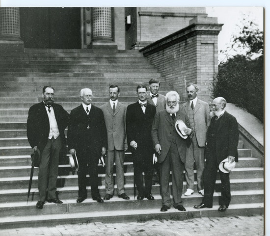 Eight executive committee members of the American Association to Promote Teaching Speech to the Deaf stand on outdoor steps for a black and white photo.