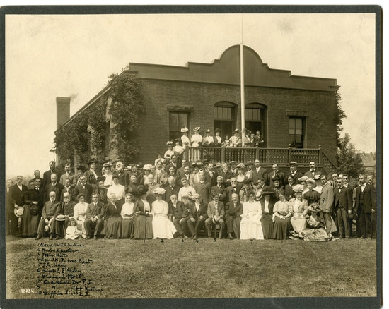 Group photograph in front of brick building.