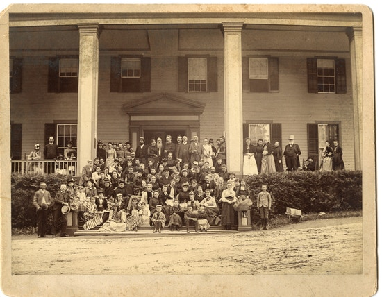 Group photograph of the first summer American Association To Promote Teaching Speech To The Deaf meeting taken on a Lake George porch with Alexander G. Bell positioned center with beard.
