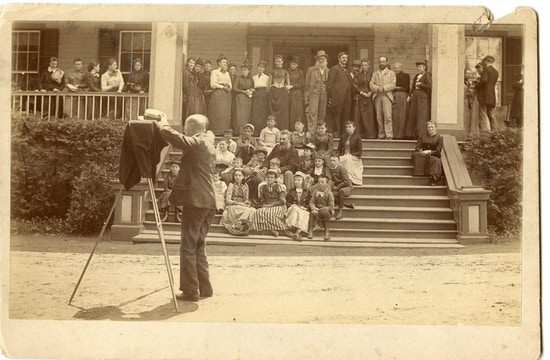 Behind the scene photograph of the group photograph of the first summer American Association To Promote Teaching Speech To The Deaf meeting taken on a Lake George porch with Alexander G. Bell. Photographer and camera are positioned left with the meeting participants in the background.