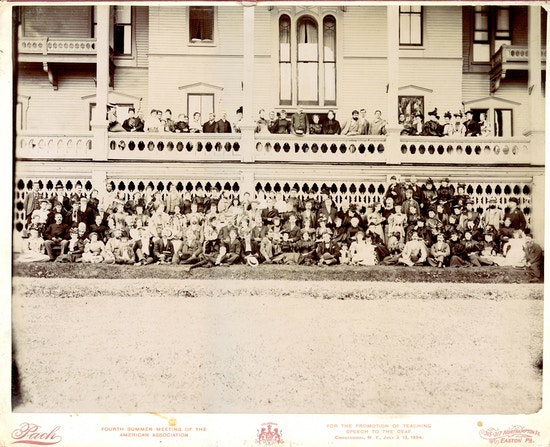 Large group photograph of American Association To Promote Teaching Speech To The Deaf summer meeting attendees wrapped above and below a large white porch in 1894.