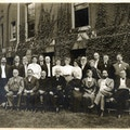 American Association To Promote Teaching Speech To The Deaf 1906 Convention photograph taken outdoors. One row of attendees sit and one row of attendees stands in front of a large wall with climbing ivy.