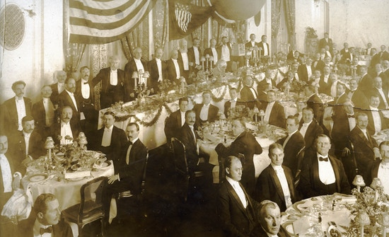 Group of formally dressed men at banquet.
