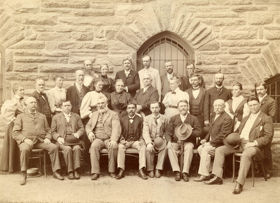 Attendees of the American Association To Promote Teaching Speech To The Deaf meeting held in 1896. Attendees pose for photograph in front of a stone building.