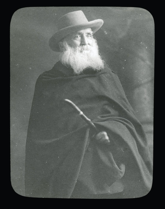 Alexander Graham Bell, facing right, wearing dark cloak and hat, grayed beard, holding cane or stick.