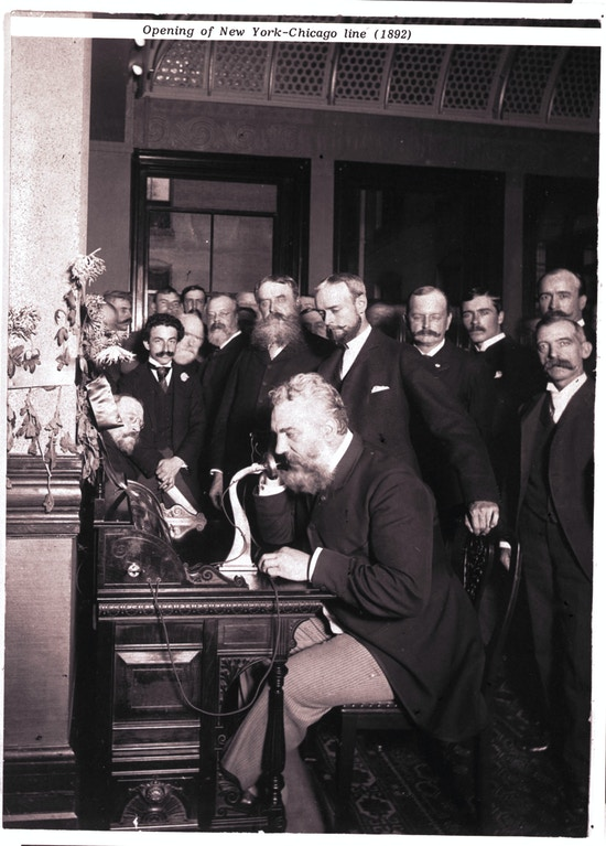Alexander Graham Bell speaks into a telephone.  A group of men in suits look on.