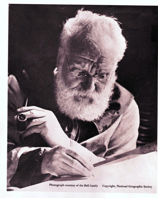 Elderly Alexander Graham Bell writing and holding pipe.