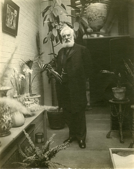 Alexander Graham Bell, standing indoors, looking at camera, surrounded by potted plants.
