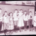 Both male and female deaf children stand in front of a chalk board to read at the Horace Mann School.