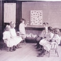 One student standing at the chalkboard and five students in the classroom sitting at the Horace Mann School.