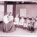 Six Horace-Mann students sit semi-circle around a teacher while one student stands left.