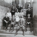Group portrait of eleven people of which are students and possibly teachers of the Horace Mann School, seated on steps.