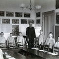 Horace Mann students and teacher stand behind desks and chairs, facing the camera in a classroom.