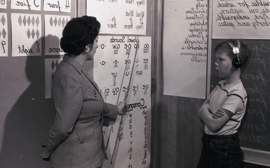 Teacher pointing to symbols printed on a large sheet of paper, facing side right.