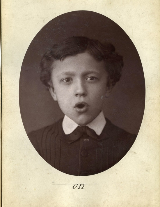 Photograph flashcard of a young boy demonstrating phonetic sounds by mouth movement.