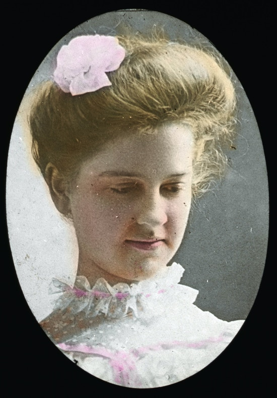 Mildred Keller with ruffled collar, looking down and to right, colored.