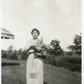 Helen Keller in the garden of her Long Island home (Forest Hills, NY), taken on her birthday by Rebecca Mack. Stands on lawn holding flowers.