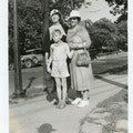 Two women and aboy in shorts standing on a sidewalk.